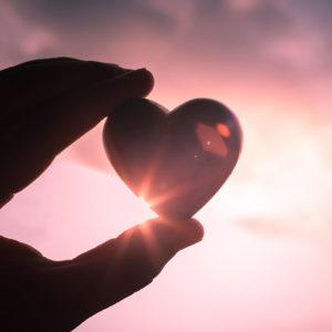 Hand Holding Glass Heart in sunlight